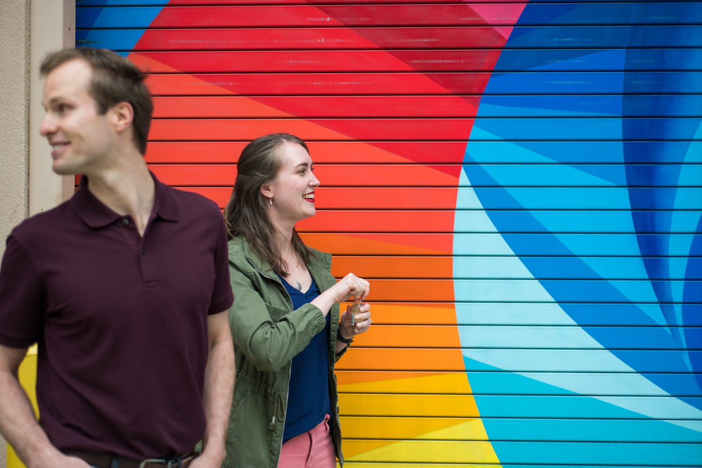 engaged couple walks by colorful mural in Durham NC