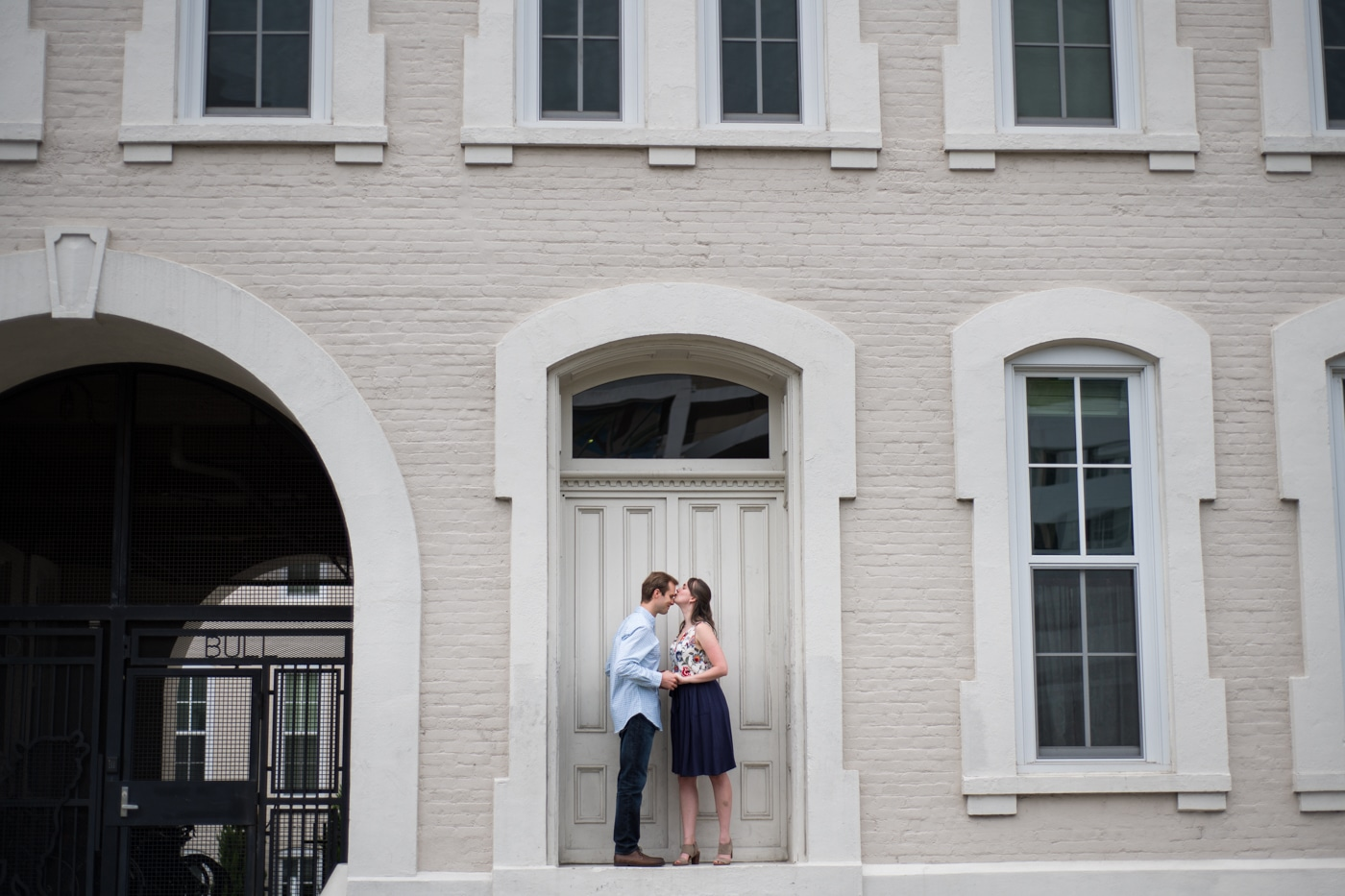 bride and groom kiss outside white building for Durham engagement session