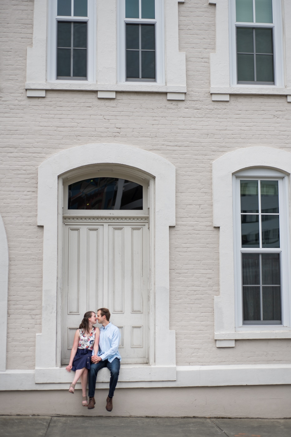 engaged couple sits on steps of doorway during Durham engagement session