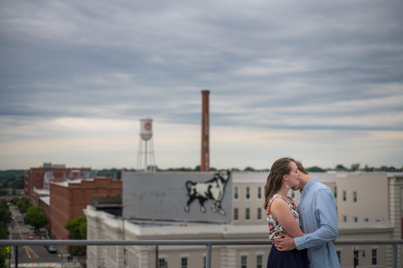 groom kisses bride's cheek on rooftop of building in Durham NC
