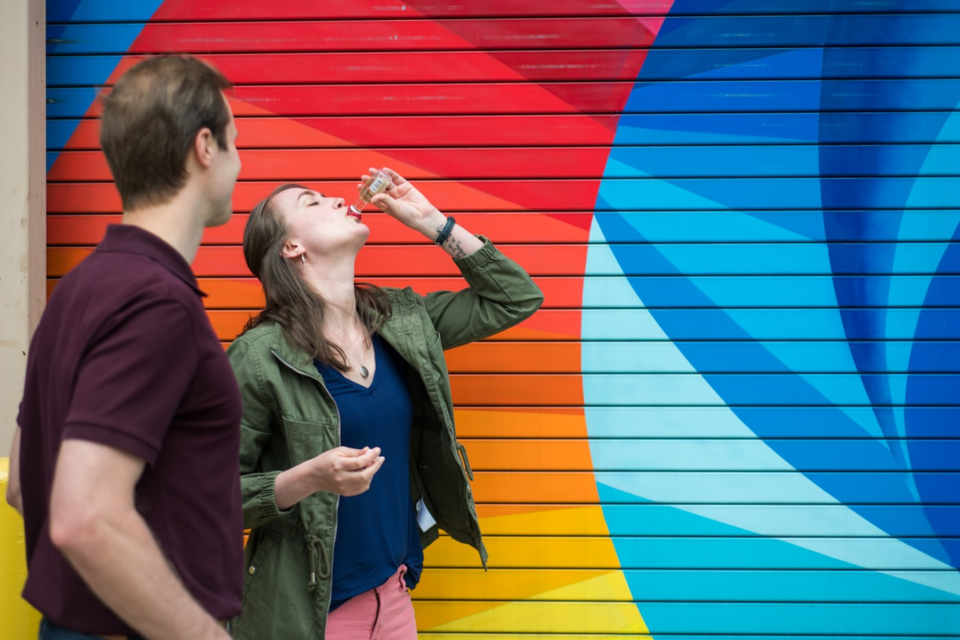 woman drinks from small bottle of alcohol during engagement photos