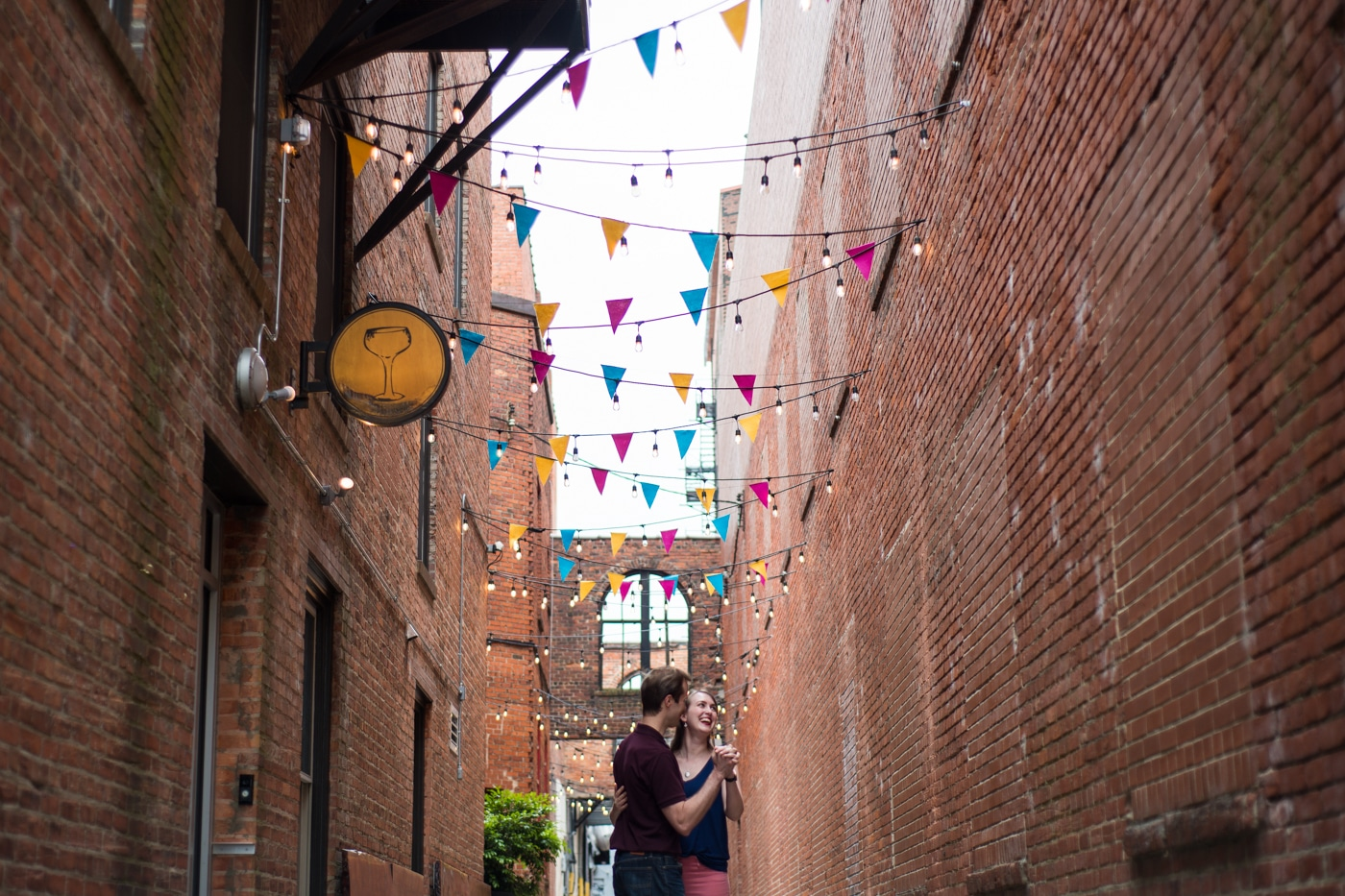 couple poses in alleyway during Durham engagement session