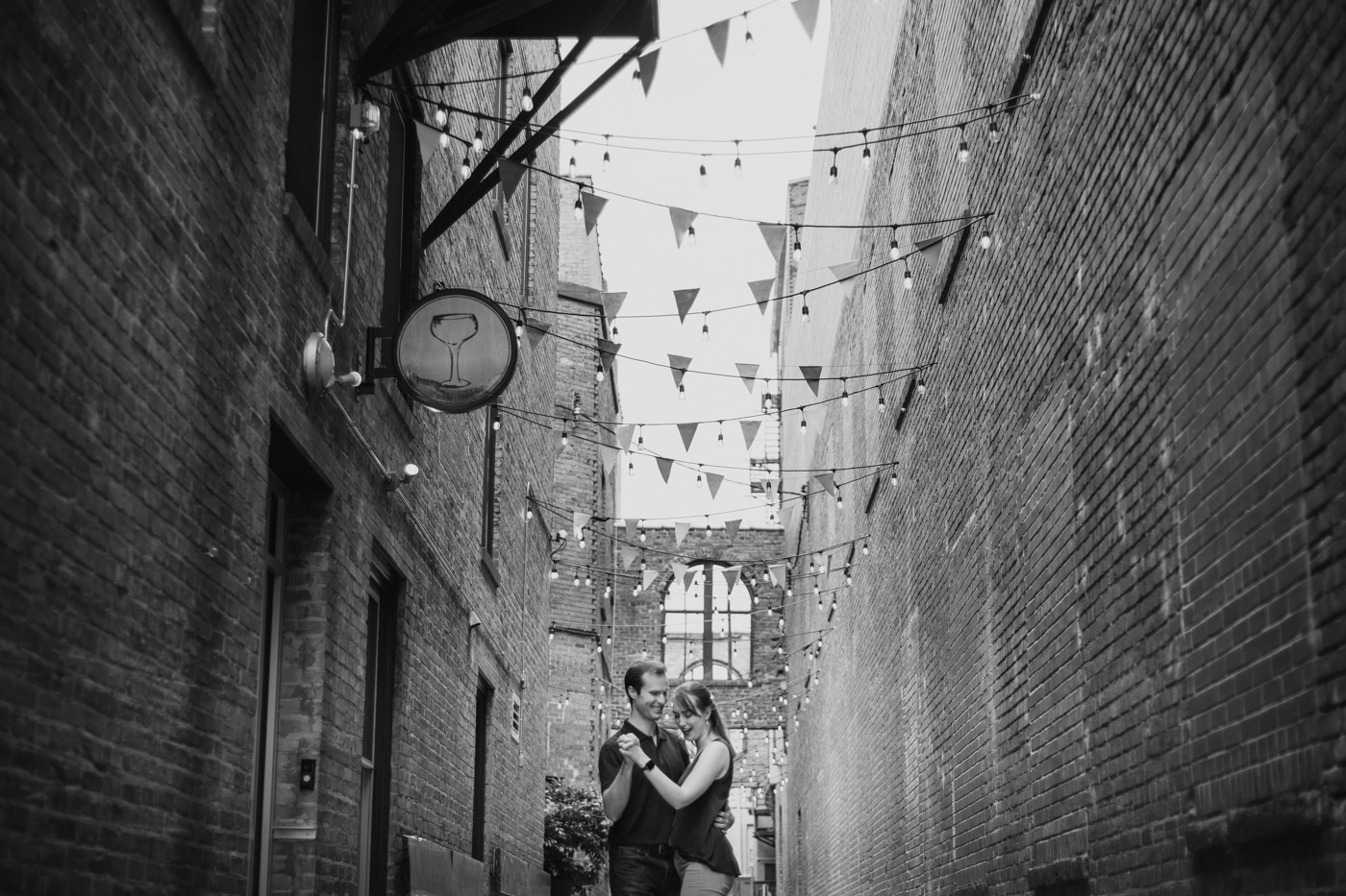 engaged couple dances under flags during Durham engagement session
