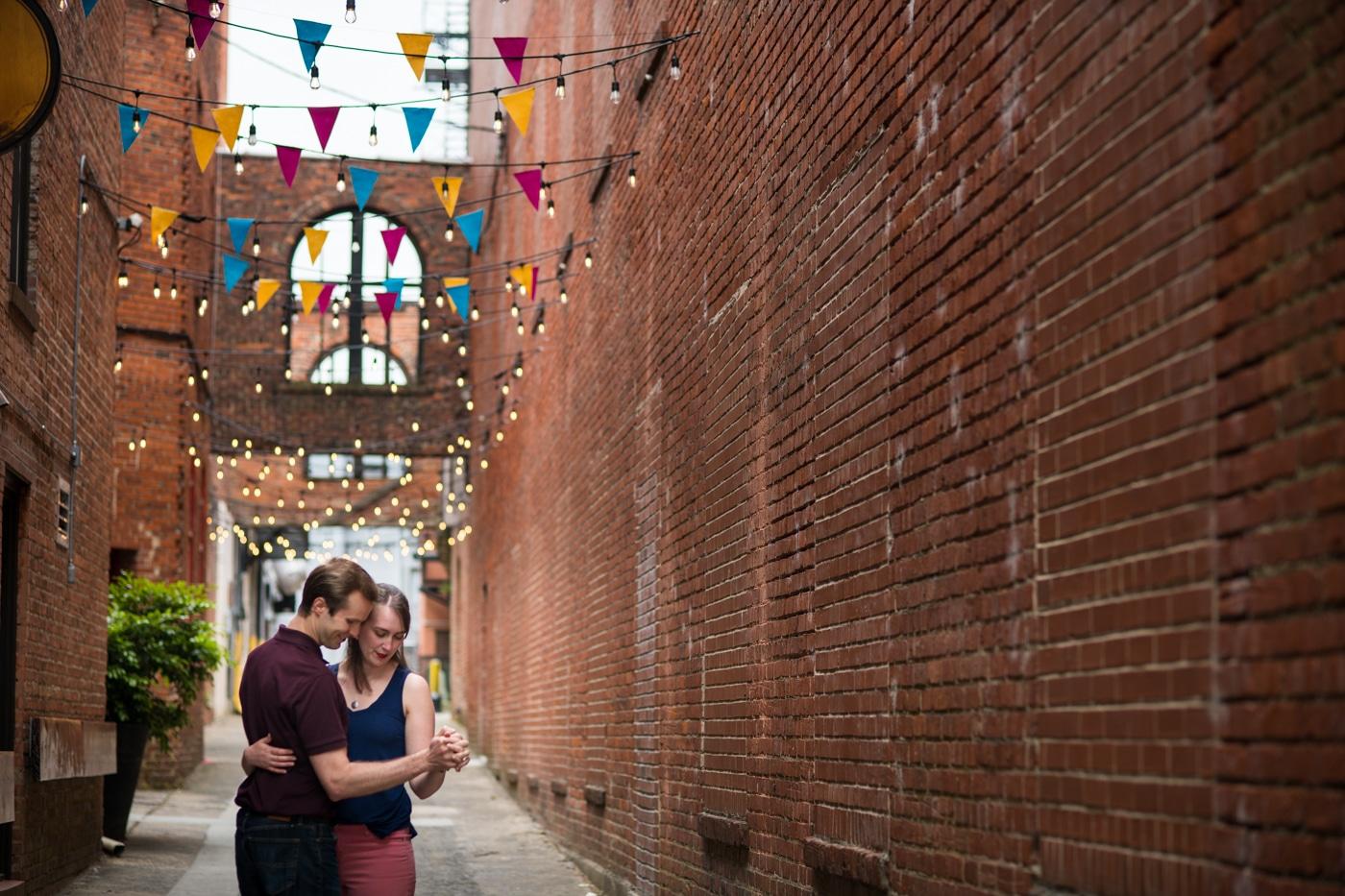 bride and groom hug in brick alleyway under colorful flags