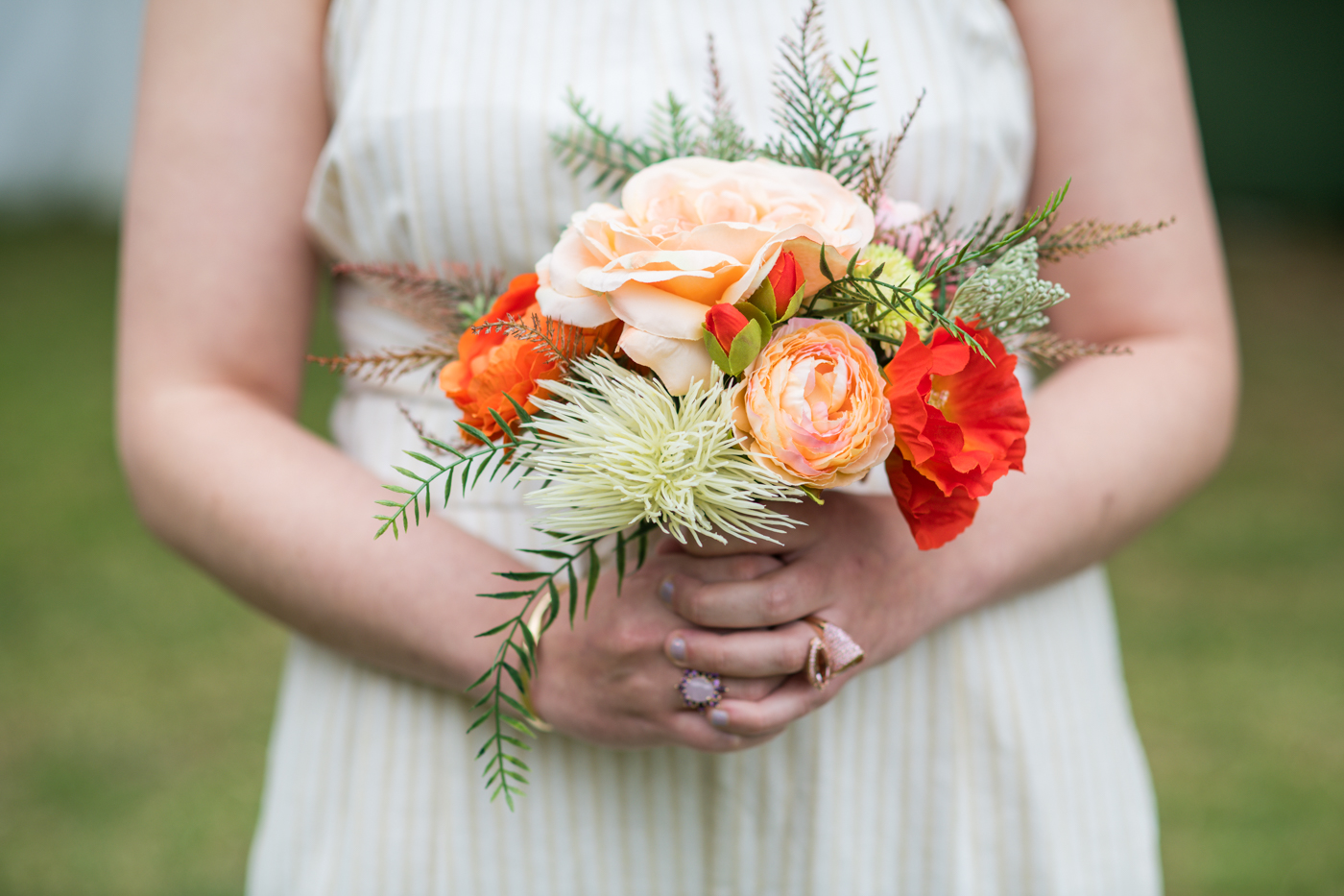 bride holds bouquet of peach and red tropical flowers