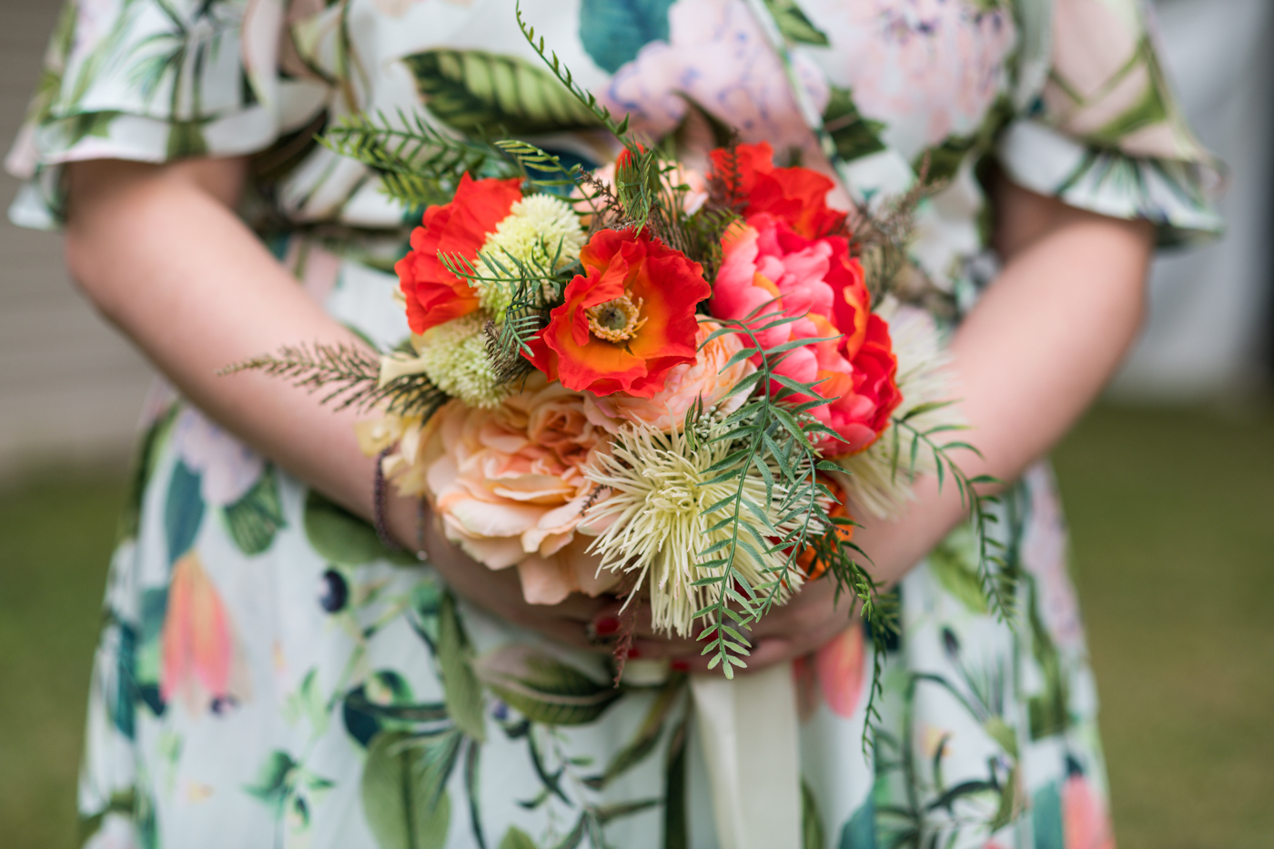 bride holds bouquet of red and green tropical flowers