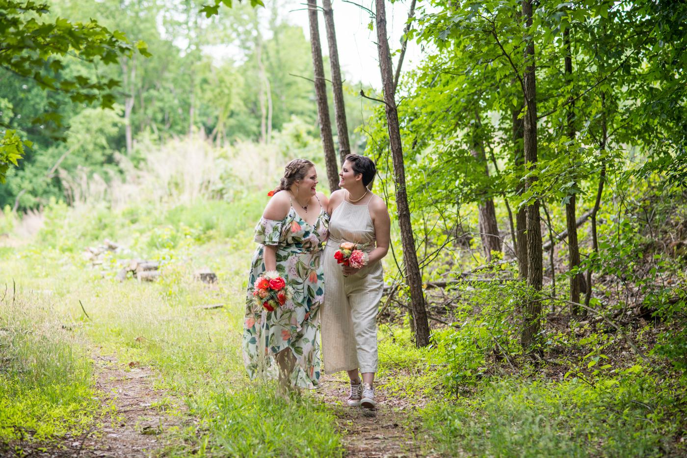 women walk through woods at Bill Scott Pavilion on wedding day