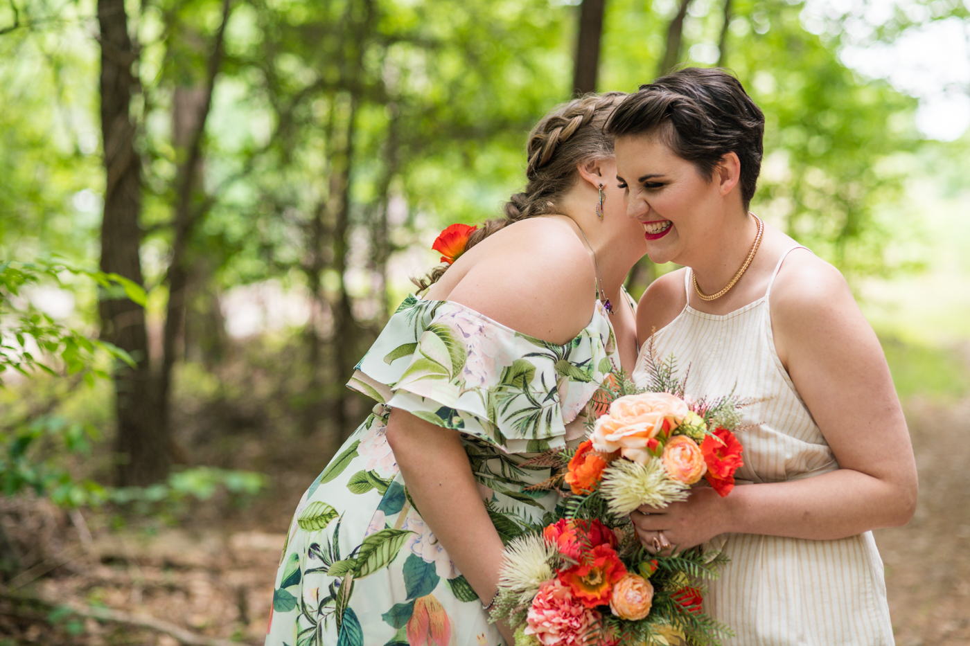 woman whispers to partner during wedding portraits in woods
