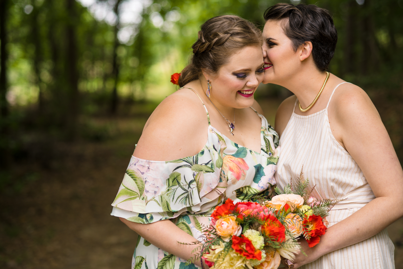 bride whispers in wife's ear during wedding portraits in Raleigh NC