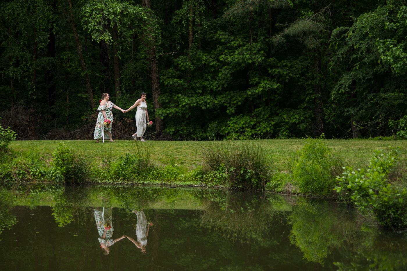 women walk by lake during wedding portraits in Raleigh NC