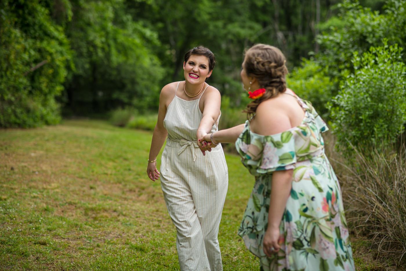 brides hold hands walking through path at Bill Scott Paviilion