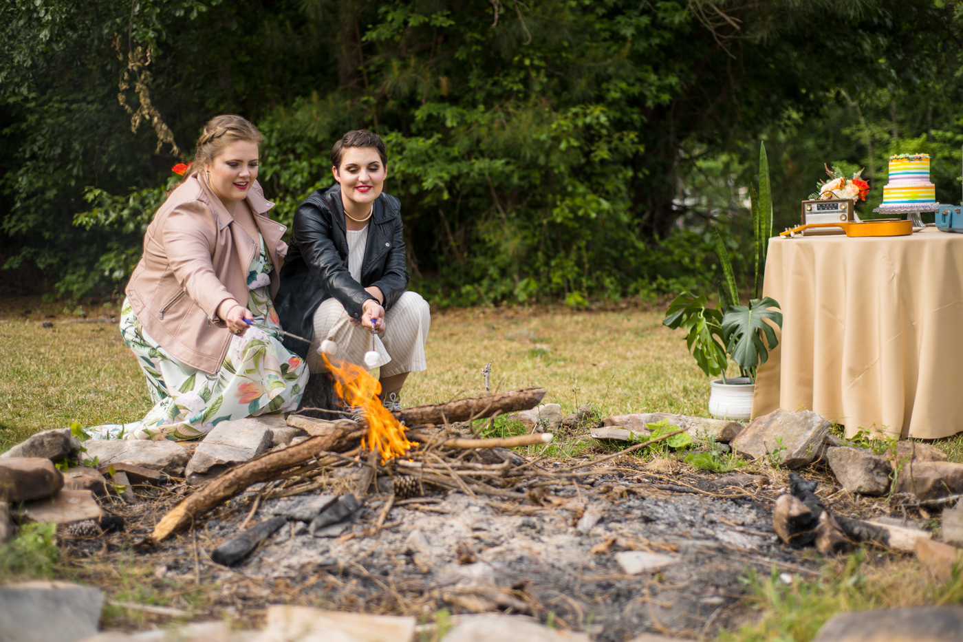 two brides sit by campfire during Green Wedding Guild styled shoot