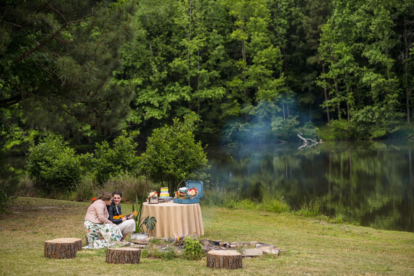 brides sit by campfire at Bill Scott Pavilion during wedding day