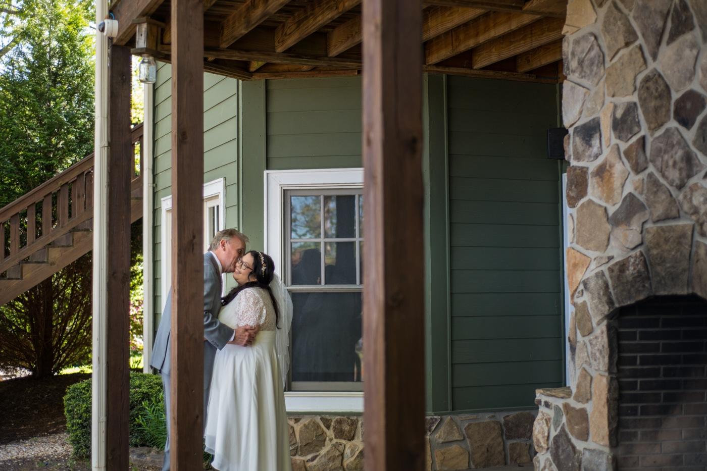 newlyweds kiss under deck at Lake Blue Ridge house