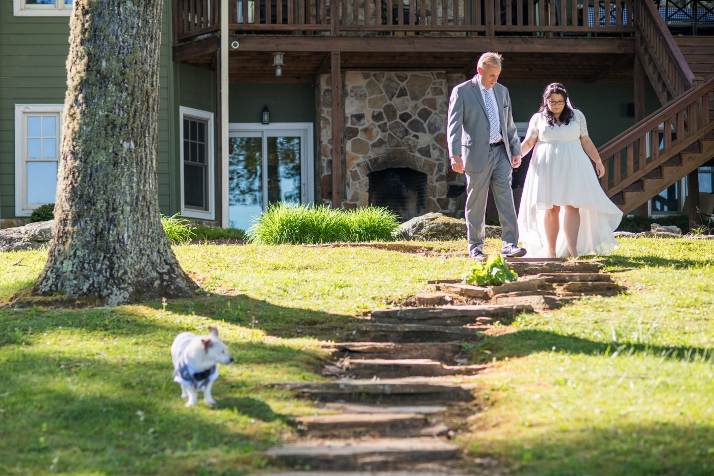 bride and groom walk down hill with dog before lakeside wedding day