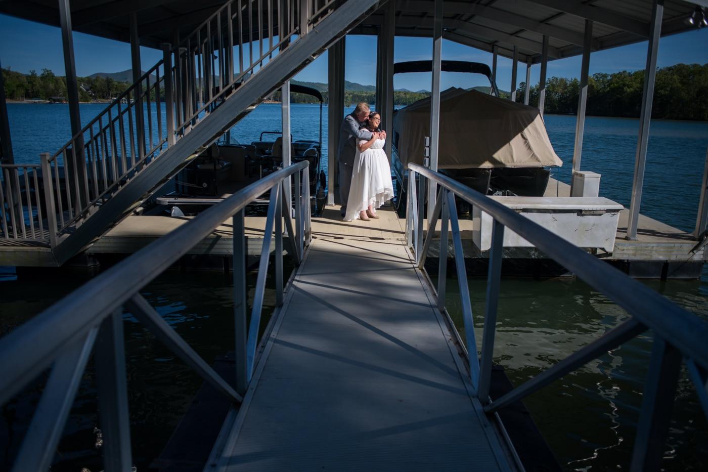 newlyweds kiss on boat dock at Lake Blue Ridge