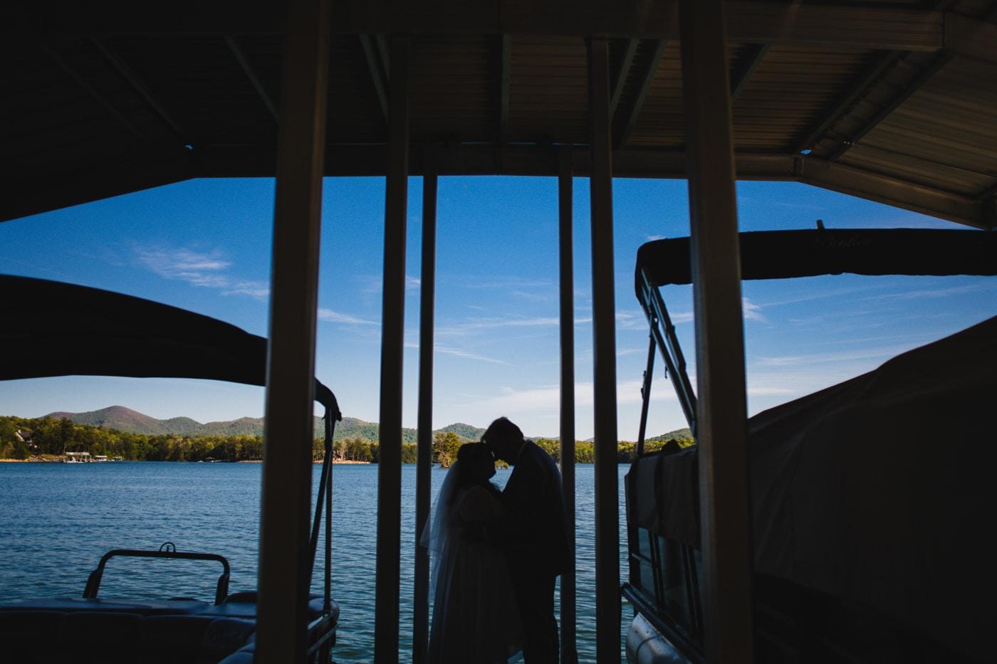 newlyweds pose between boats at Lake Blue Ridge