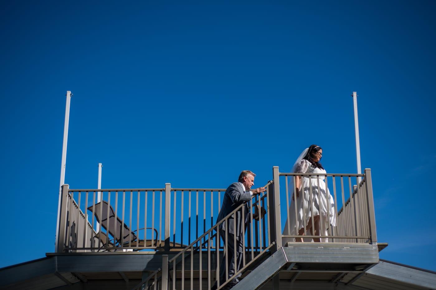 groom follows bride up to deck at boat marina