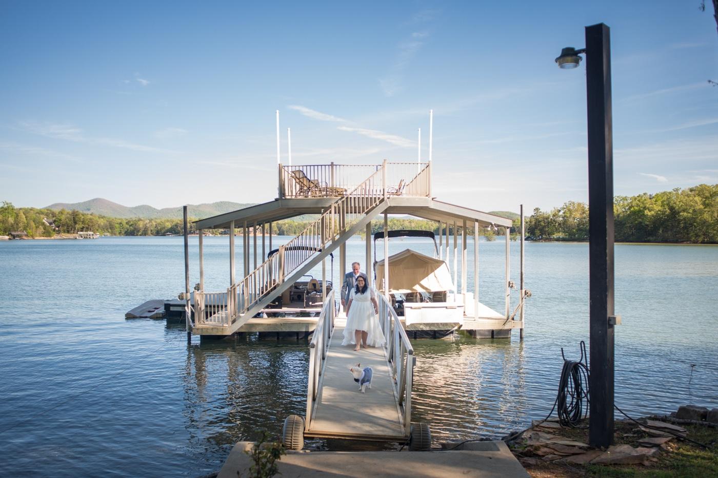 newlyweds walk down boat marina on Lake Blue Ridge wedding day