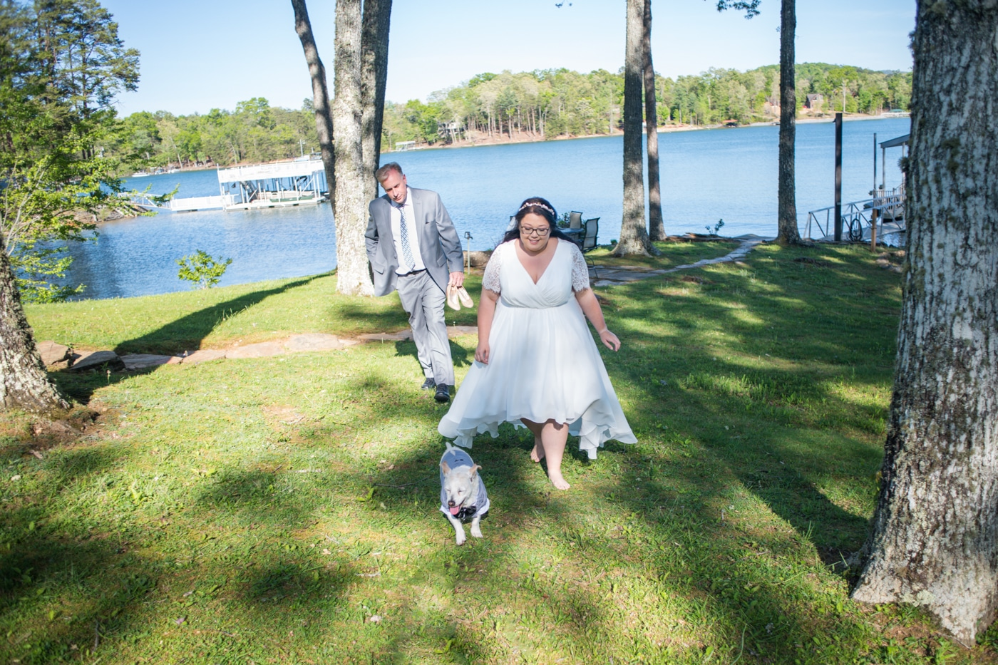 bride chases after dog during wedding photos by lake