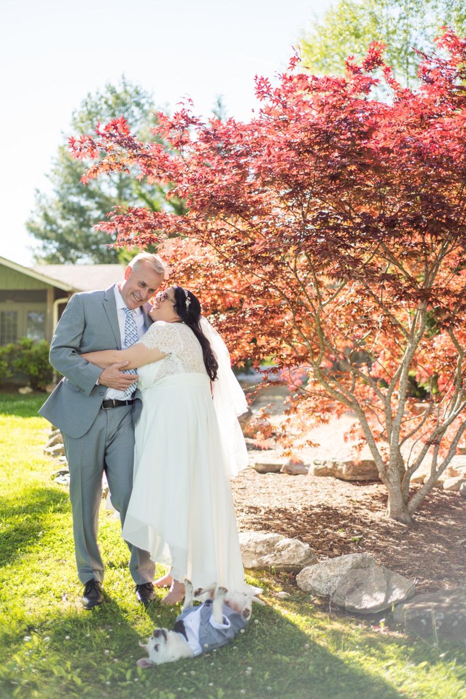 bride and groom hug by red tree before Lake Blue Ridge wedding day