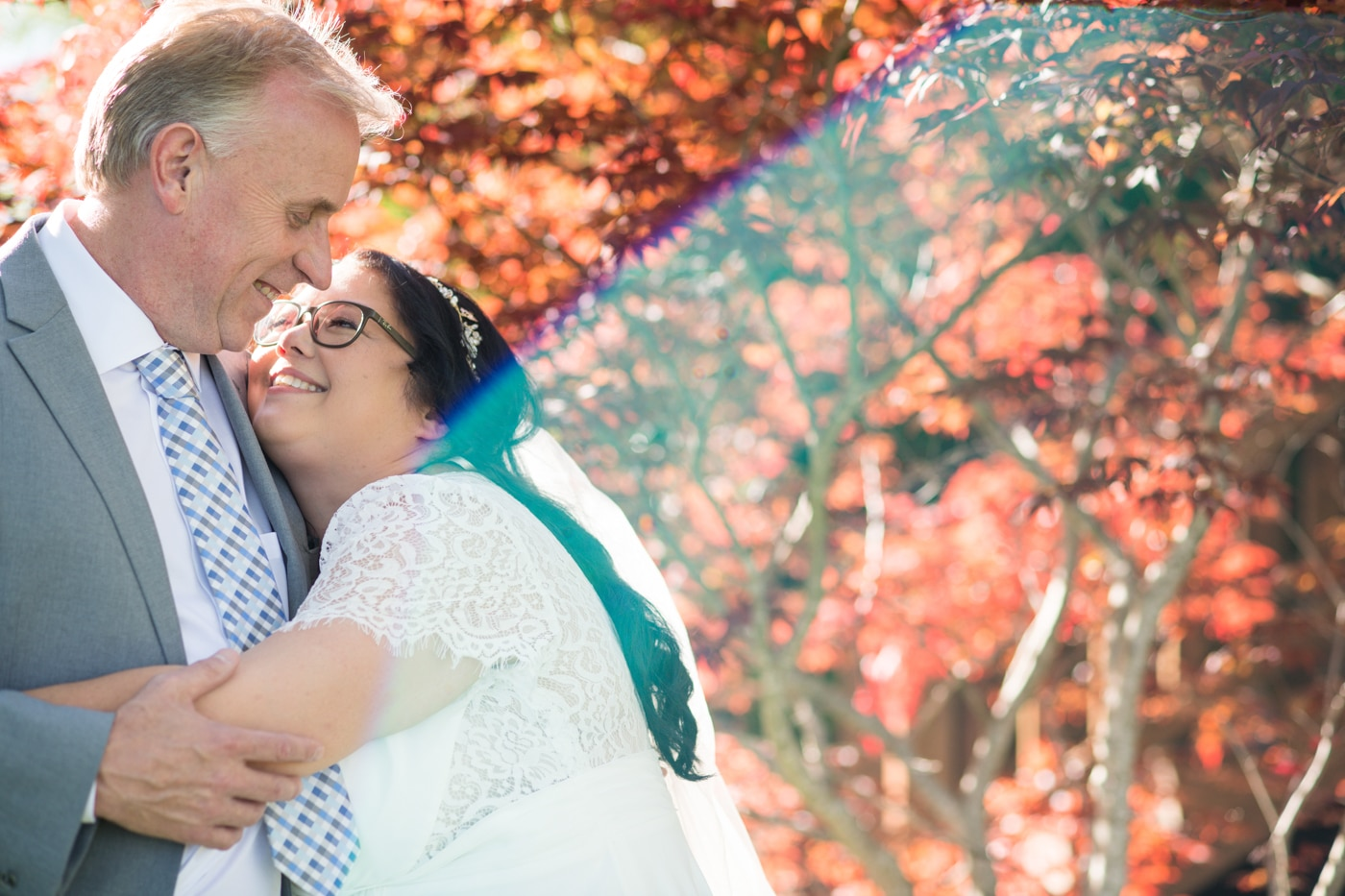 bride hugs groom looking up at him