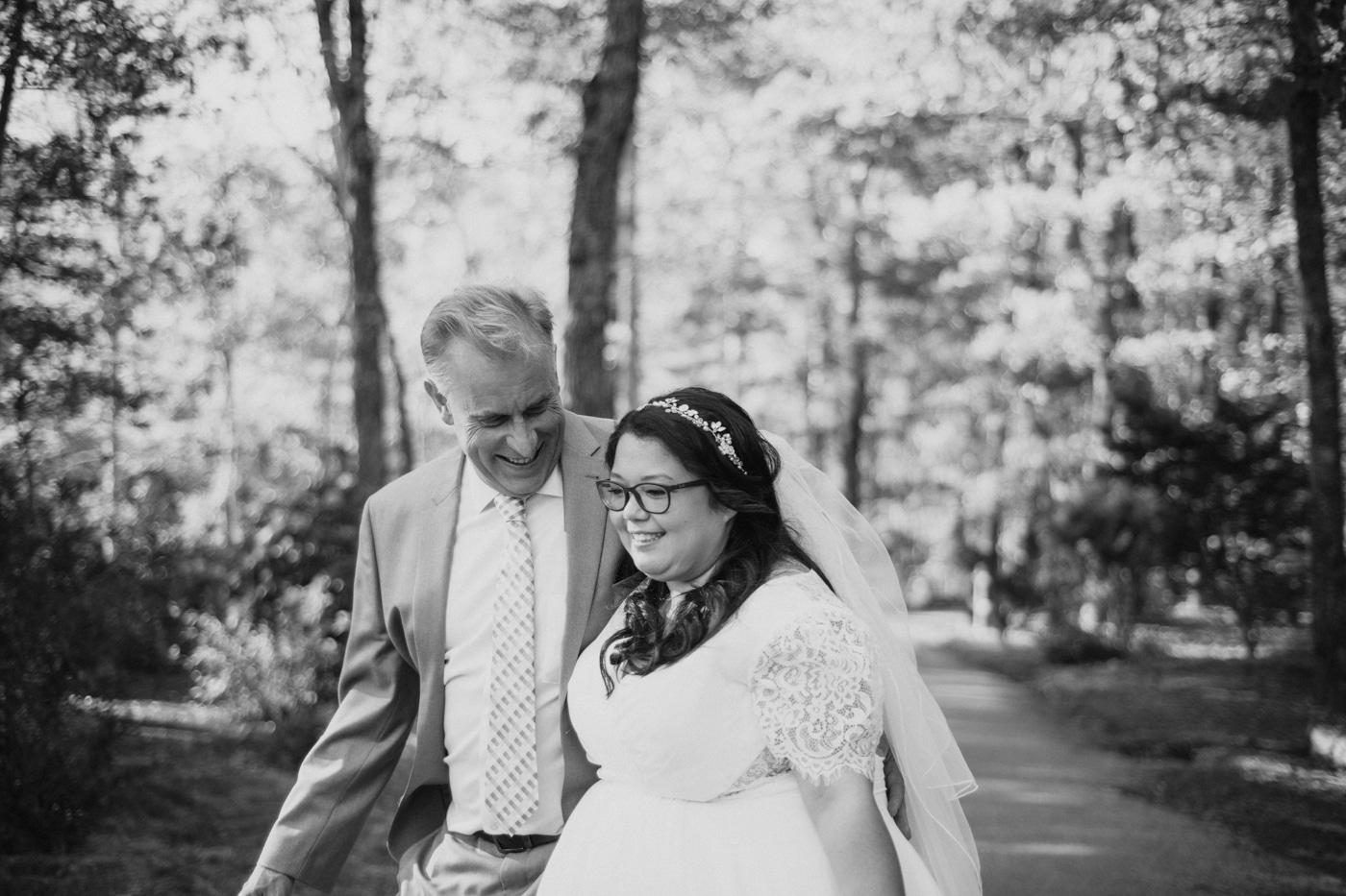 bride and groom walk through woods at Lake Blue Ridge