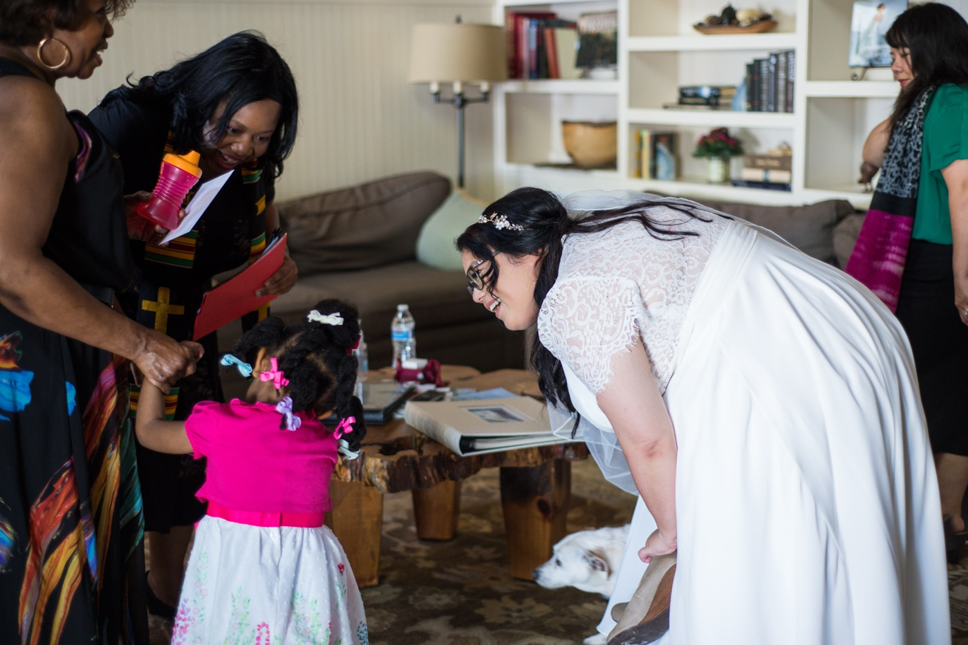 bride talks to young guest during wedding day prep