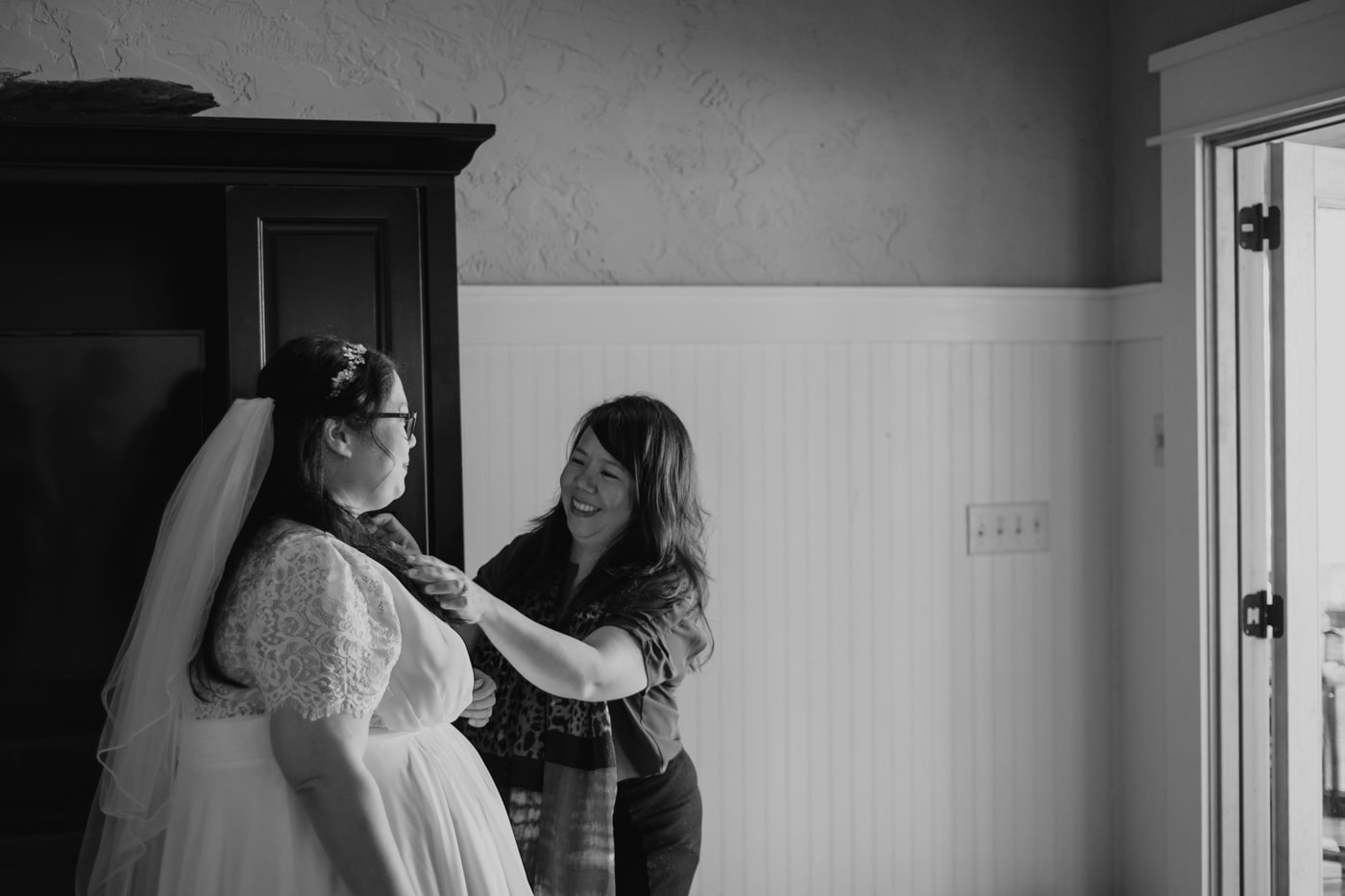 woman helps bride with jewelry on wedding day