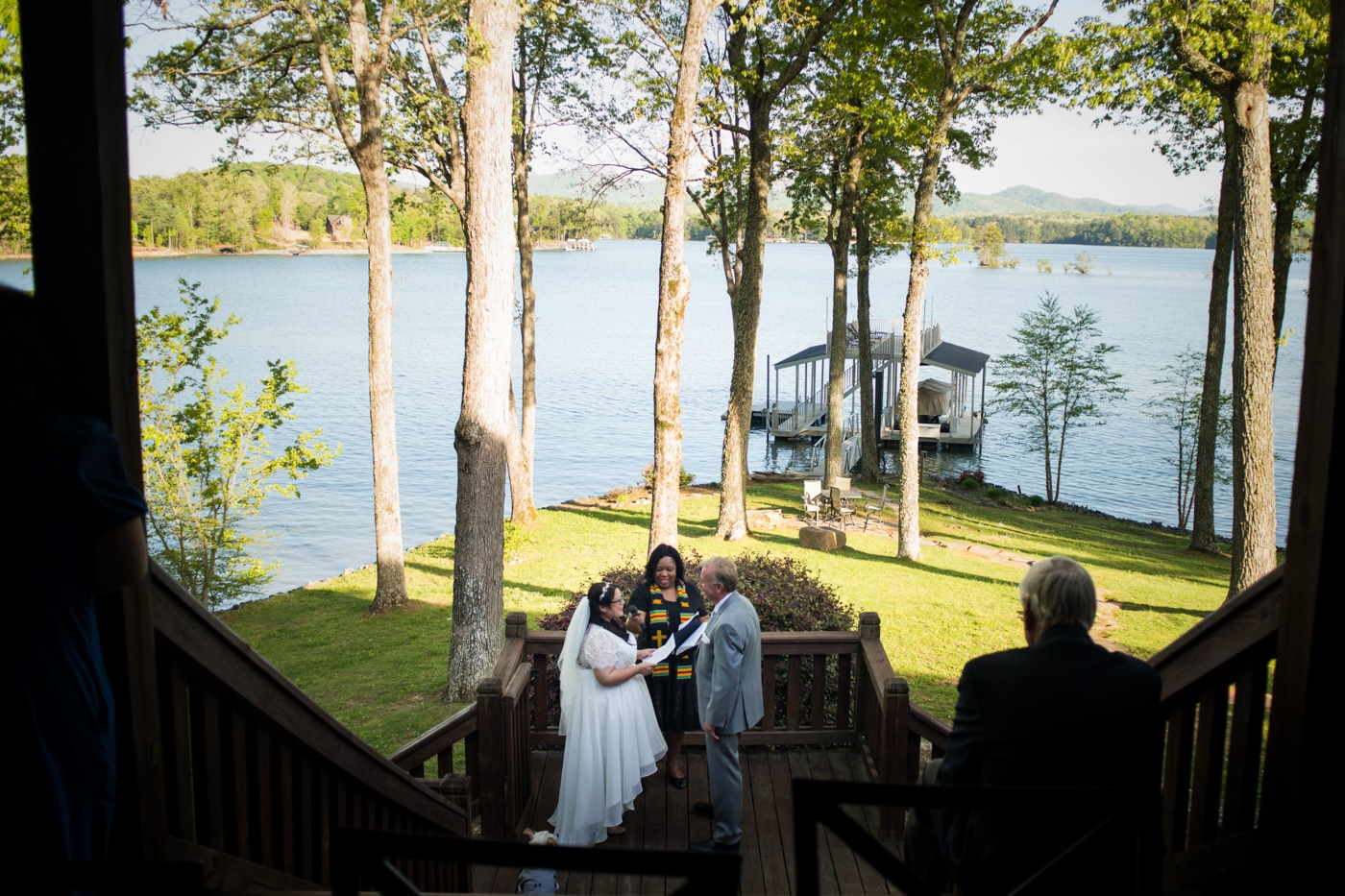 bride and groom exchange vows during lakeside ceremony
