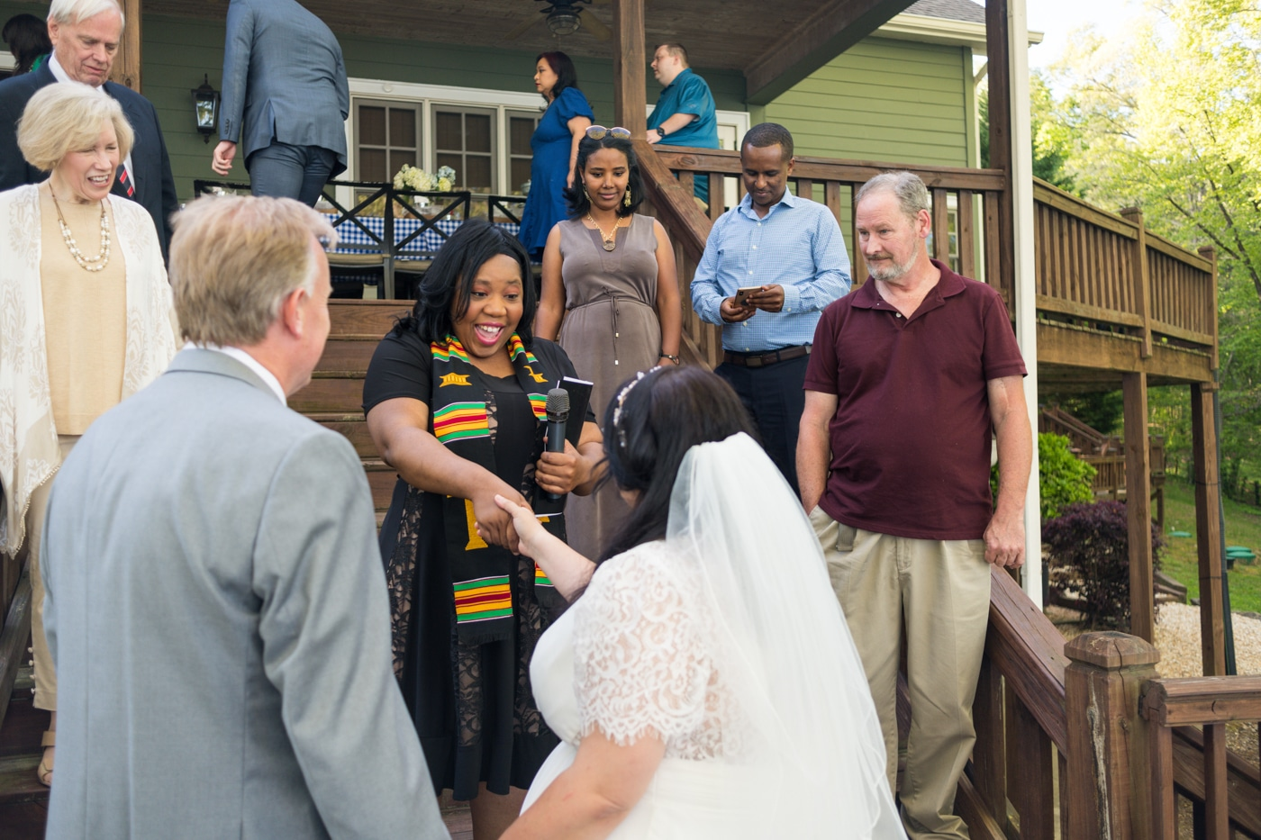 officiant looks at bride's hand during wedding photos