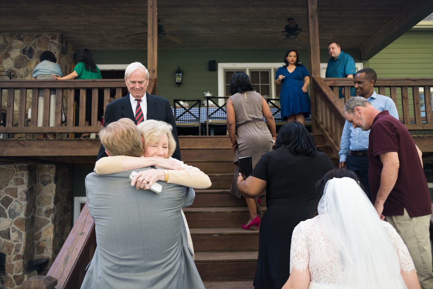 family hugs bride and groom