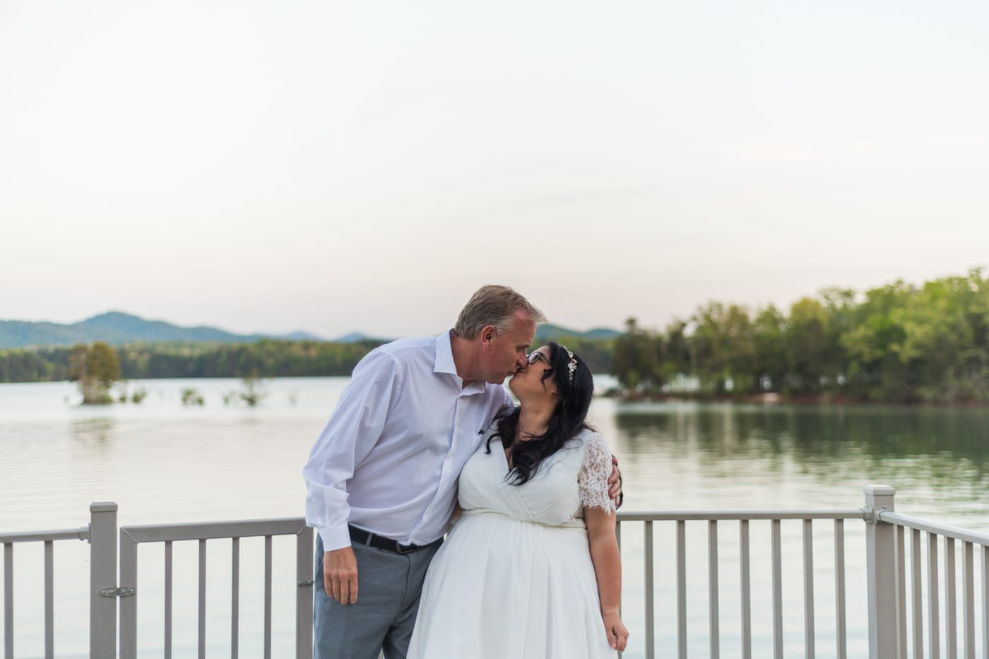 bride and groom kiss in front of Lake Blue Ridge