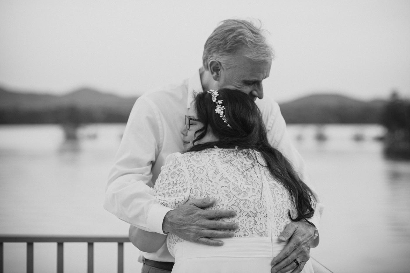 bride and groom hug on Lake Blue Ridge