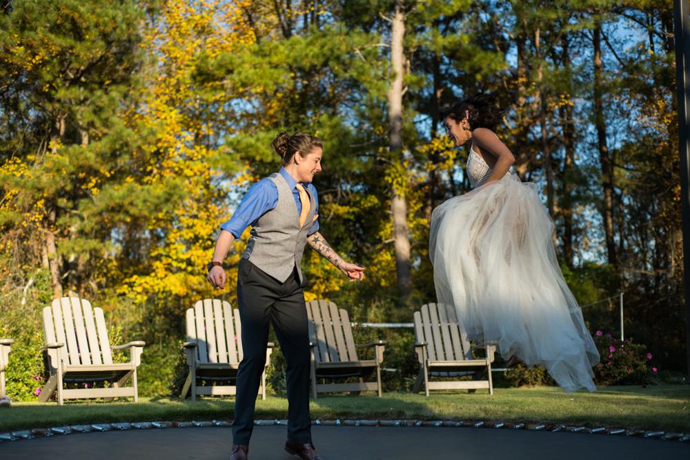 brides jump on trampoline on wedding day